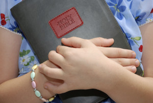 A Little Girl Holds On To Her Father's Bible.